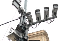 Four security cameras on the street - building in background - cloudy Stock Footage