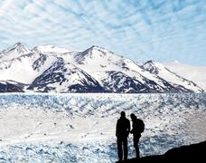 silhouette of a couple admiring beautiful view of glacier and mountains. - stock photo