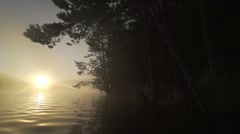 Sunrise from a mountain lake with huge pines, surrounded by morning fog Stock Footage