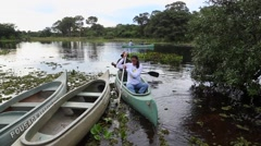 Couple riding canoe in Pantanal River, Brazil Stock Footage