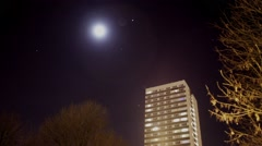 Time lapse the moon and a city apartment tower block Stock Footage