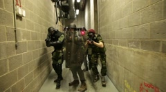 sas, military, police or swat team walking down corridor with guns aimed - stock footage