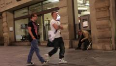 well dressed men pass sick homeless man on street next to bank - stock footage