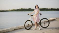 Girl with bicycle on a water and decline background in the summer. Stock Footage