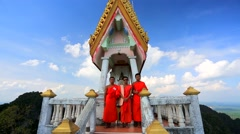 Three young buddhist monks at Wat Tham Seua (Tiger Cave) temple Stock Footage