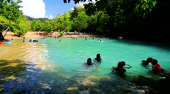 Tourists bath in the emerald pool in the tropical forest Stock Footage