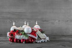 advent wreath in red and white with four burning candles. - stock photo