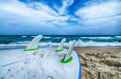 surfboard and fins awaiting to get into ocean water - stock photo