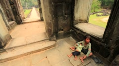Cambodian boy holding a baby at Baphuon temple Stock Footage