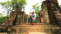 Cambodian girl holding a baby at Baphuon temple Stock Footage
