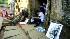 Boy draws a picture at Ta Prohm Temple Stock Footage