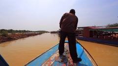 Man steers a boat on a canal of Tonle Sap lake Stock Footage