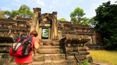 Young male backpacker visiting Angkor Wat Temple. Southern Gate. - stock footage