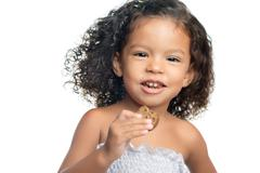 Joyful little girl with an afro hairstyle eating a chocolate cookie Stock Photos