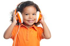 Lttle girl with an afro hairstyle enjoying her music on bright orange headpho Stock Photos