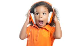 Excited little girl with an afro hairstyle enjoying her music on bright orang Stock Photos