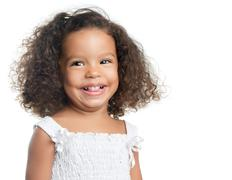 Little girl with an afro hairstyle smiling and wearing a white dress Stock Photos