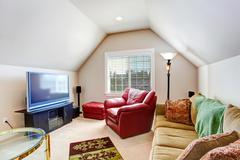 Small living room with red armchair and tv Stock Photos