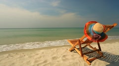 Sunlounger with hat standing on beautiful tropical beach - stock footage