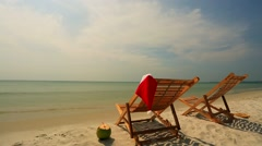 Sunloungers with Santa hat and coconut Stock Footage