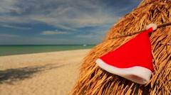 Santa hat laying on a straw umbrella. Stock Footage