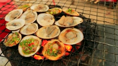 Grilling clams on a beach - stock footage