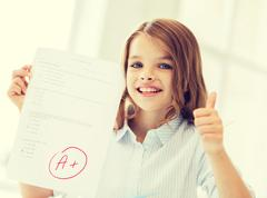 Stock Photo of smiling little student girl with test and A grade
