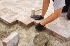 Worker installing paver Stock Photos