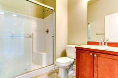 simple bathroom interior with vanity cabinet and glass door shower - stock photo
