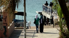 Western Asia Red Sea Jordan Aqaba 008 two young women with headscarf from rear Stock Footage