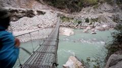 Backpacker crossing Marsyangdi river Stock Footage