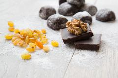 two pieces of black chocolate and a wallnut on it. - stock photo