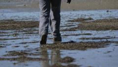 Hiker walking on a beach at low tide leaving footprints. Stock Footage