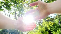 man raising hands into the sky - sun beam - sun light flare - carefree happy - stock footage