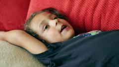 Boy lying on red couch and singing a song Stock Footage