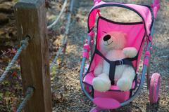 Teddy bear fastened in the baby carriage Stock Photos
