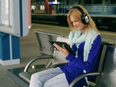 Happy girl sitting on platform and listening music on tablet Stock Footage