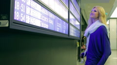 Girl looking on departures board and talking on cellphone Stock Footage