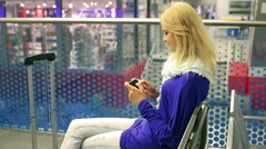 Happy girl tweeting on cellphone and sitting on the station - stock footage