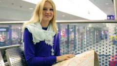 Girl reading map on the station and smiling to the camera Stock Footage