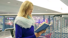 Girl checking time while reading book and hurrying up Stock Footage