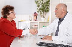 Appointment at doctor: older woman talking with a specialist. Stock Photos