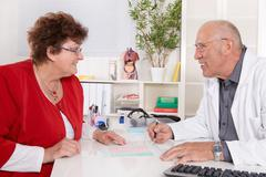 portrait of an older doctor talking with a female patient. - stock photo
