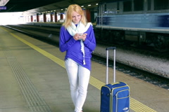 Happy girl standing on platform and tweeting on smartphone Stock Footage