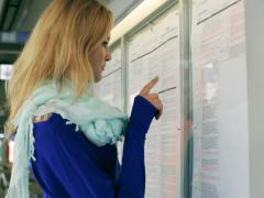 Young woman reading information board on platfrom Stock Footage