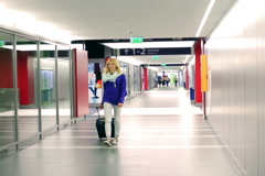 Girl walking on corridor and pulling suitcase Stock Footage