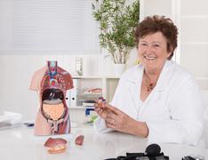 portrait of happy older senior doctor explaining the human body. - stock photo
