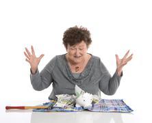 Happy female pensioner after smashing her piggy box. money concept senior peo Stock Photos