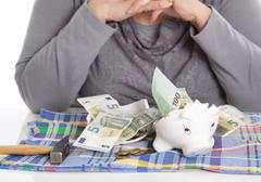 Happy female pensioner after smashing her piggy box. money concept. Stock Photos
