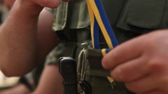 Soldier ties a blue and yellow ribbon on body armor Stock Footage
